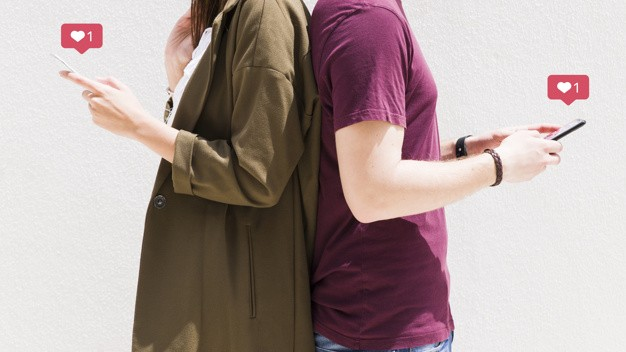 couple-standing-back-back-using-cellphone-with-love-messages-icons-against-wall