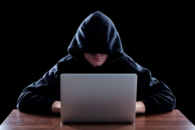 hacker-dark-hoody-sitting-front-notebook